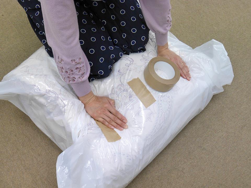布団・枕の丸洗い&高温乾燥サービスは圧縮してテープでとめる